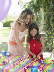 mother and daughter (7-9) laying table for birthday party