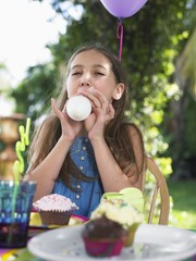 young girl (10-12) blowing up balloon at birthday party