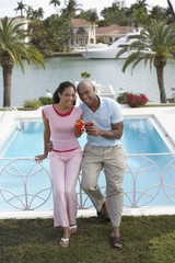 couple holding cocktails leaning on pool banister