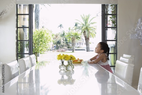 girl (5-6 years) sitting at dining table  side view