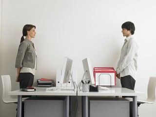 two office workers standing facing each other
