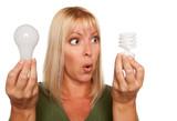 Funny Woman Holding Energy Saving and Regular Light Bulbs poster