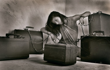 Attractive brunette chained to heavy suitcases.