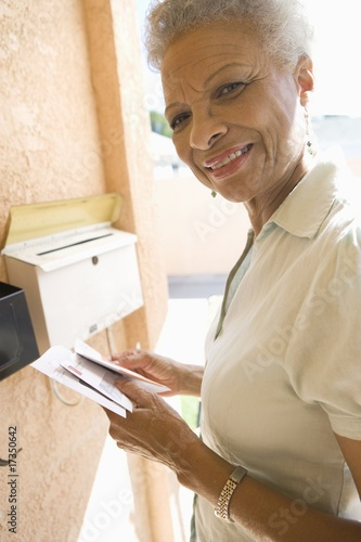 woman collecting mail from letterbox