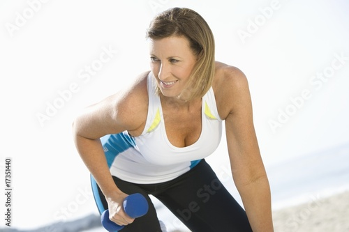 Sporty woman at the beach lifting hand weights