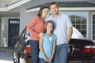 Family outside house with car