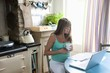 Pregnant woman sitting at kitchen table with laptop