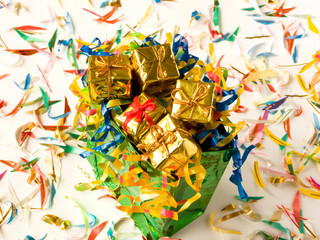 Bag full of small golden gifts around confetti. Shallow DOF.
