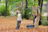 mother and son throwing autumn leaves in park