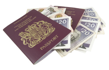 two british passports and cash isolated on white background