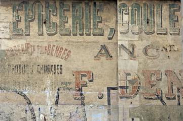 Alte,verwitterte Werbung an einer Fassade in Bayeux,Frankreich