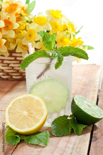 Cold glass of beverage with slice of lime and lemon