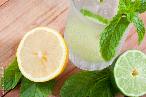 Sliced lemon and limes on wooden table next to cold drink