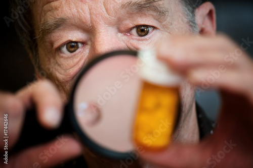 Man examining instructions on medicine bottle