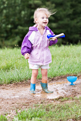 Cute little girl playing in the mud with ice cream scoops.