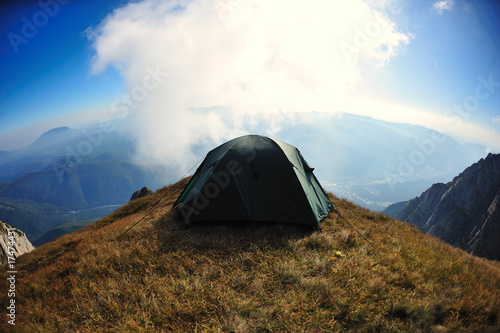 Tent on mountain cliff edge with blue sky
