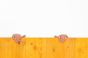 Boy`s hands on wooden fence trying to reach the top.