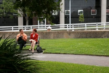 Man and woman park bench talking then walking