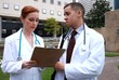 Doctor nurse outside downtown talking over test results
