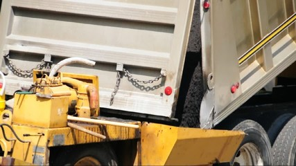 Dump truck loading a asphalt finisher with fresh asphalt