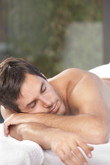 man relaxing on towel at the spa