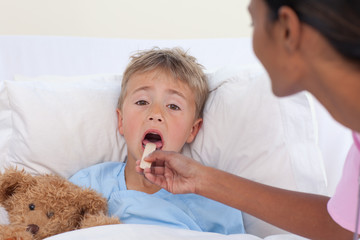 Nurse checking little boy throat in hospital