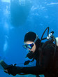 Scuba Diver Checking Gauges under the Boat