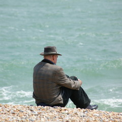 Man wearing his hat by the sea
