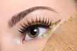 female eye witha false eyelashes and golden make-up