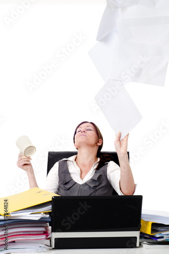 Business women at desk throwing paper up in air