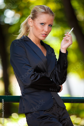 Young business woman smoking cigarette