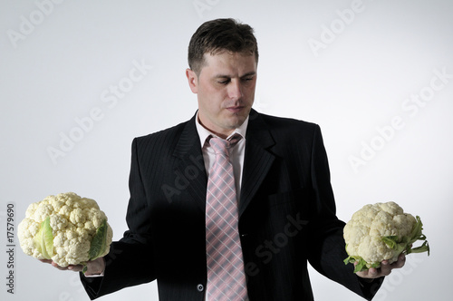 man evaluating two cauliflowers poster
