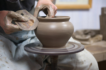 Hands of an artisan working on a potter's wheel