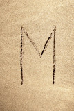 Alphabet letter M handwritten in sand poster