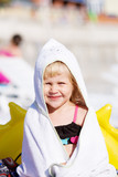 Little girl with a towel on the beach