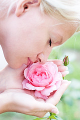 Young pretty woman enjoys a smell of  pink rose
