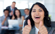 Happy businesswoman with thumbs up in office