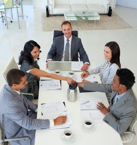 Businesswoman and businessman shaking hands in a meeting