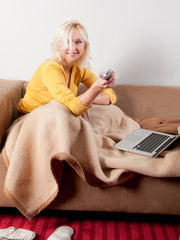 young woman relaxing on sofa with laptop and whatching TV