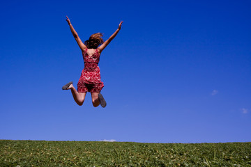 Woman jumping for joy on a green hillside!