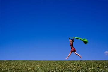 Woman running along a green hill, free in summer