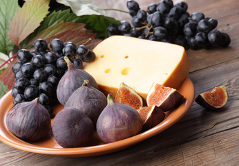 Figs and grapes in rustic plate