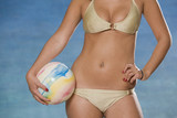 Woman in bikini holding beach ball.