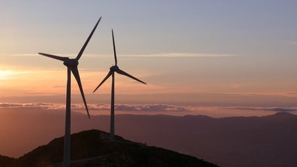 Wind turbine generator in the mountains at sunset