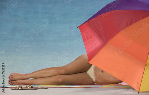 Woman in bikini under beach umbrella.
