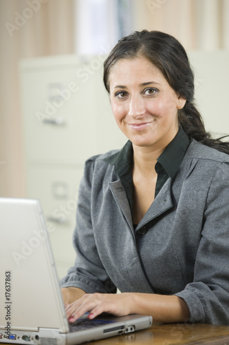 Young woman with laptop in her office.