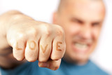 Aggressive man with words LOVE embossed in his knuckles