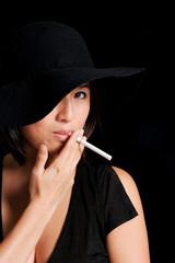 Girl in black hat smokes a cigarette