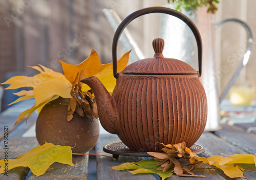 autumn tea - still life with japanese teapot and maple leaves an