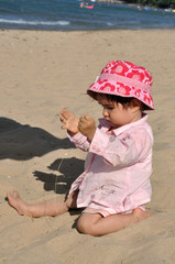 Baby playing with sand on the beach